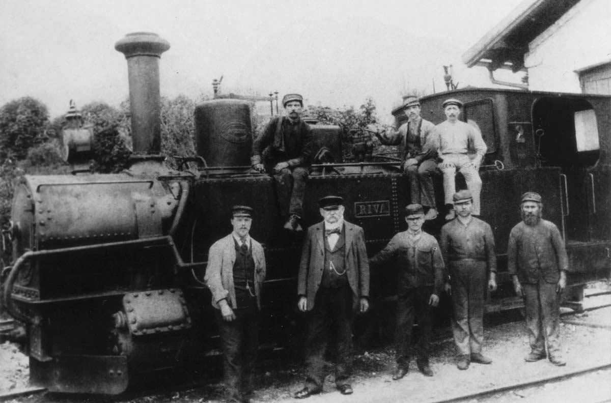 """Personale in posa davanti alla locomotiva """"Riva"""", costruita dalla ditta Krauss & Co. di Linz. In servizio fin dal 1891, viene successivamente utilizzata in Galizia e in Romania per essere infine trasportata negli Stati Uniti a servizio del parco dello zoo di Omaha. (Collezione Rudolf Schmidt)"""